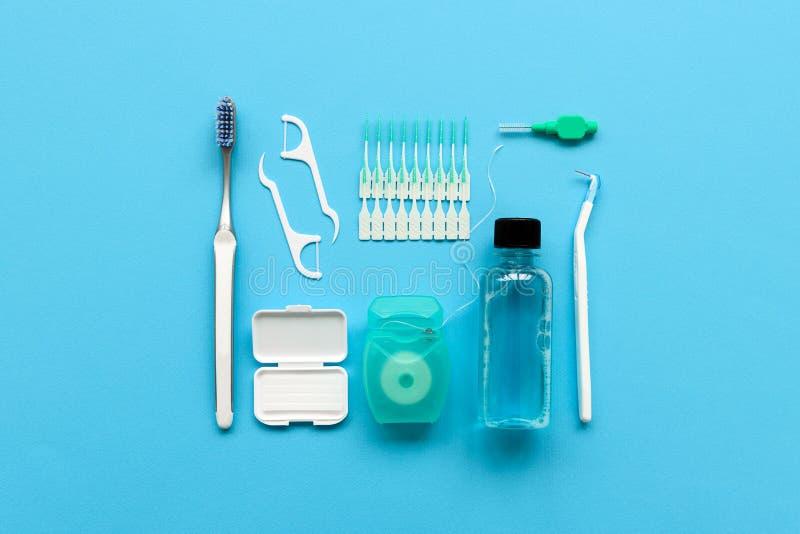 Ferramentas diferentes para cuidados dent?rios no fundo azul Escova de dentes, limpador, floss, flossers, cera para cintas e esco imagens de stock