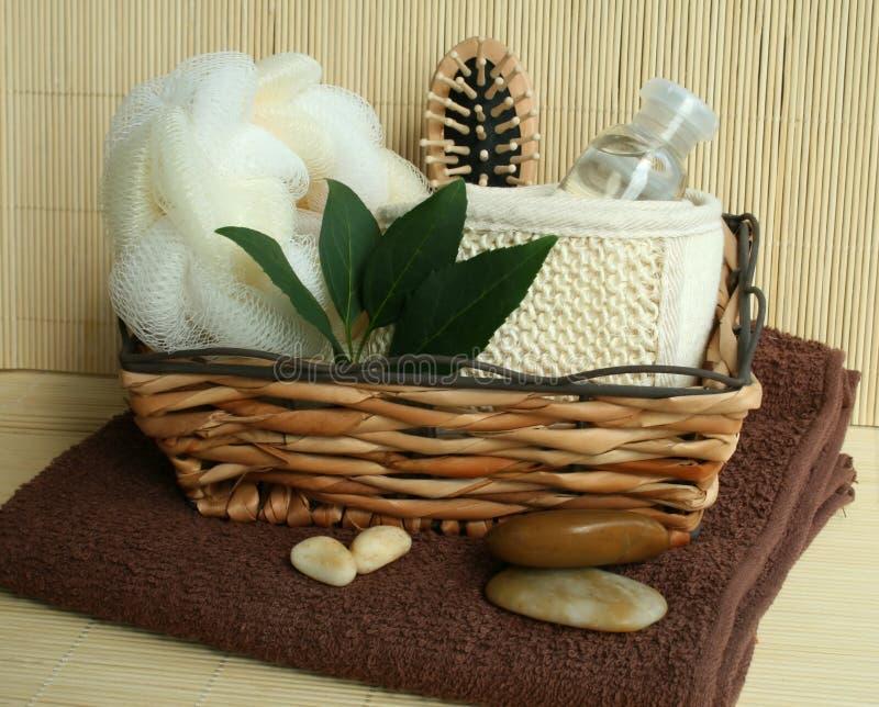 Ferramentas do banho na cesta e na toalha de madeira imagem de stock