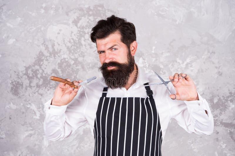 Ferramentas do barbeiro Barbeiro na lâmina e nas tesouras do equipamento do cabeleireiro do avental Corte de cabelo profissional  imagem de stock royalty free