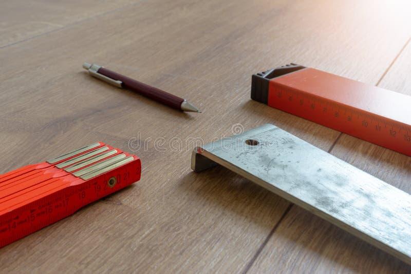 Ferramentas e equipamento para colocar do assoalho estratificado, nível de espírito, régua de dobradura, puxando o ferro imagem de stock
