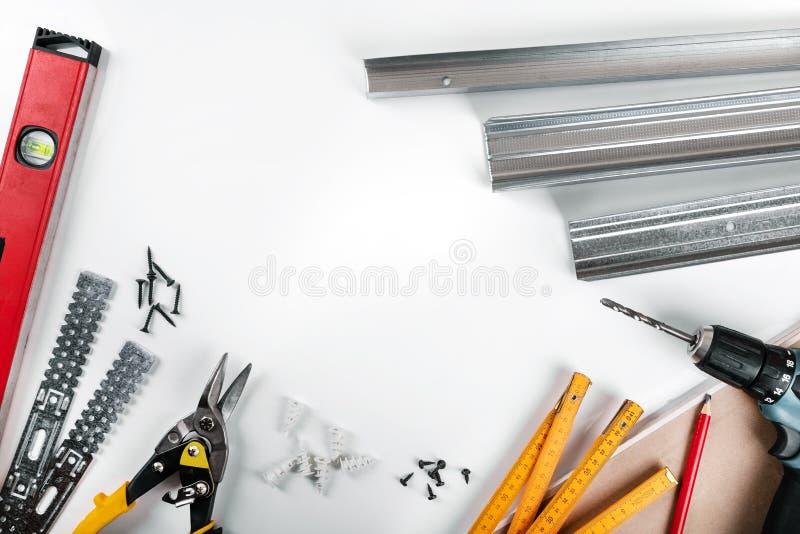 Ferramentas e prendedores da montagem do Drywall no fundo branco imagens de stock