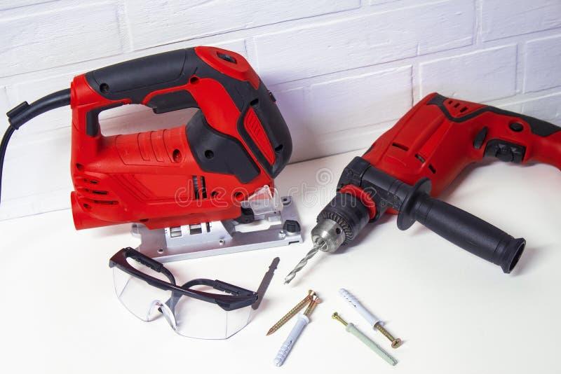 Ferramentas elétricas de construção profissionais para a madeira e o metal Serra e broca elétricas do gabarito com vidros de segu foto de stock