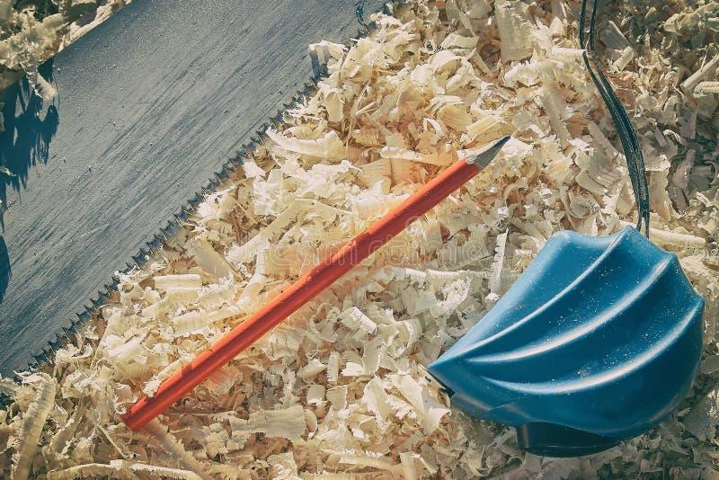 Ferramentas importantes de medição da fita e do lápis ao ver as placas e os platbands de madeira imagem de stock