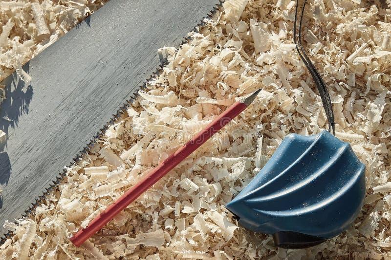 Ferramentas importantes de medição da fita e do lápis ao ver as placas e os platbands de madeira imagens de stock