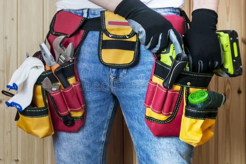 Ferramentas na correia para ferramentas O construtor está guardando uma chave de fenda elétrica Foco seletivo fotos de stock royalty free