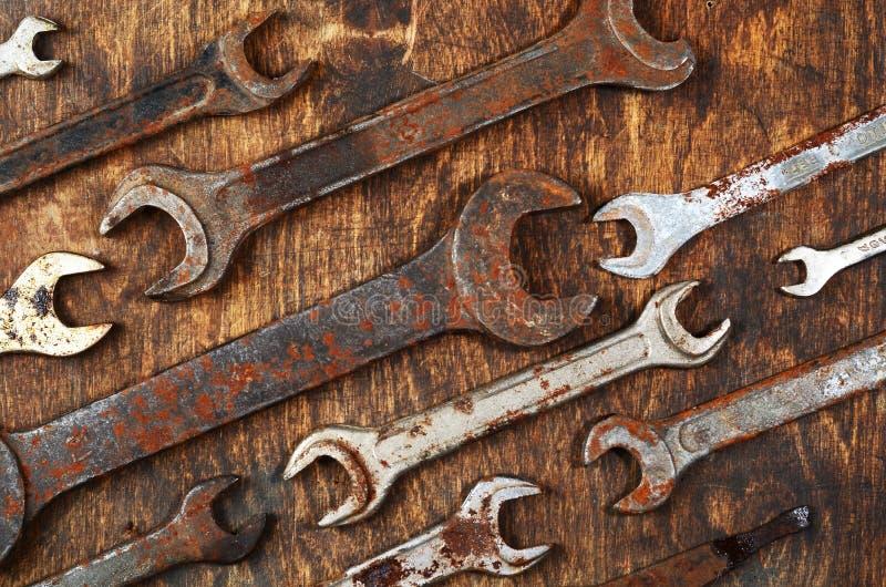 Ferramentas oxidadas do metal do ferro da chave do grupo do metal que encontram-se em t de madeira escuro imagens de stock