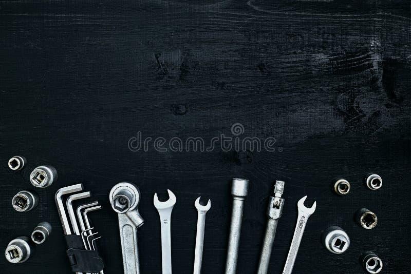 Ferramentas para o automóvel do trabalho ou do reparo no fundo de madeira preto Vista superior imagens de stock royalty free