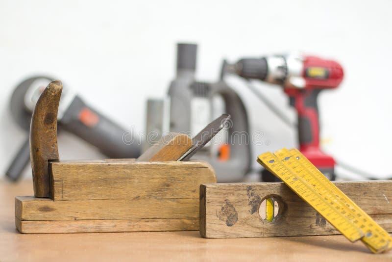Ferramentas velhas da carpintaria no primeiro plano Ferramentas elétricas novas no fundo foto de stock