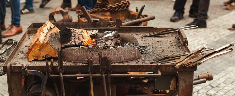Ferramentas velhas do ferreiro na feira medieval Batente, martelo, fogo, corrente Soldador na cidade a oficina da forja da rua Fo foto de stock royalty free