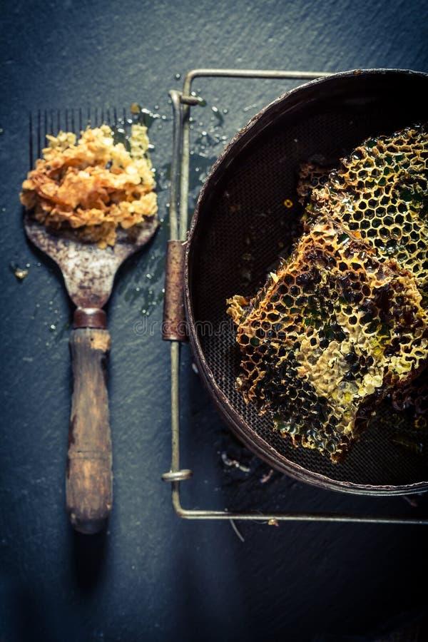 Ferramentas velhas para a apicultura com o favo de mel completo do mel foto de stock