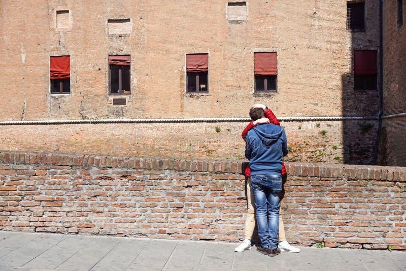 FERRARA, ITALIA 17 DE JUNIO DE 2017: Pares de los individuos jovenes que se besan y que abrazan en la arena pública fotografía de archivo libre de regalías