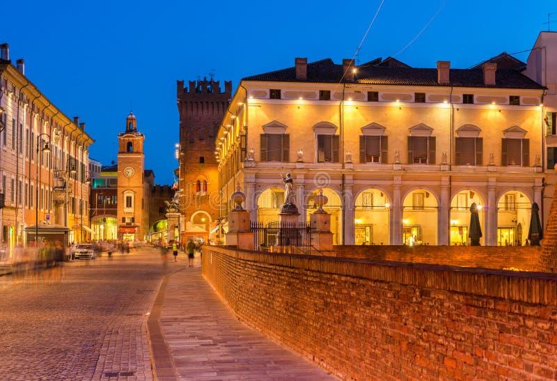 Ferrara Italien: Aftonsikt av den historiska mitten av Ferrara Upplyst gammal arkitektur och stadsgränsmärkena arkivbilder