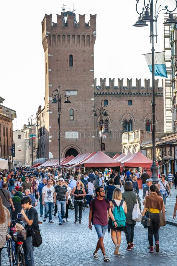 Historic center of the city of Ferrara in Italy. Many people walk in the street. royalty free stock photography