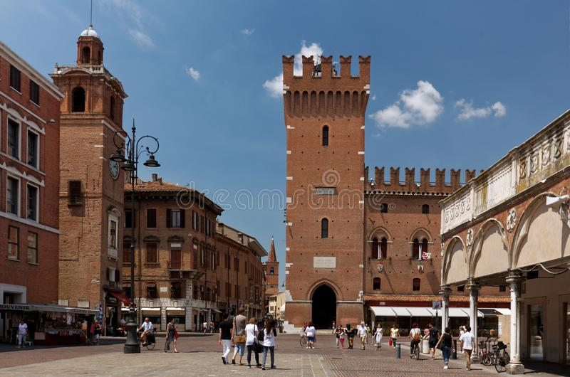People on Piazza Trento in Ferrara, Italy. Ferrara, Italy - June 17, 2017: People walking on Piazza Trento against the Ferrara Town Hall. Begun in 1245, the City royalty free stock image