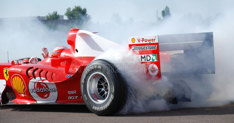 Ferrari F1 Michael Schumacher Donut Smoking Tyre at Fiorano Circuit, Italy. One Handed Driving with Wave During Donut. stock image