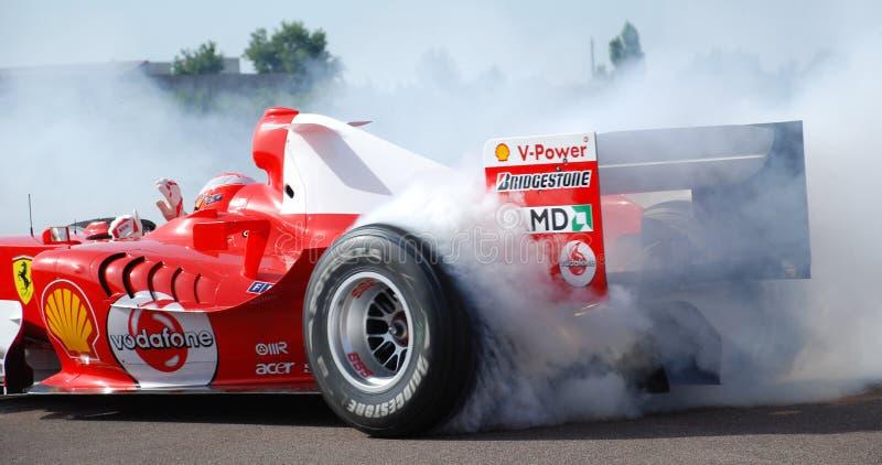 Ferrari F1 Michael Schumacher pączka dymienia opona przy Fiorano obwodem, Włochy Jeden Wręczał jeżdżenie z fala Podczas pączka obraz stock