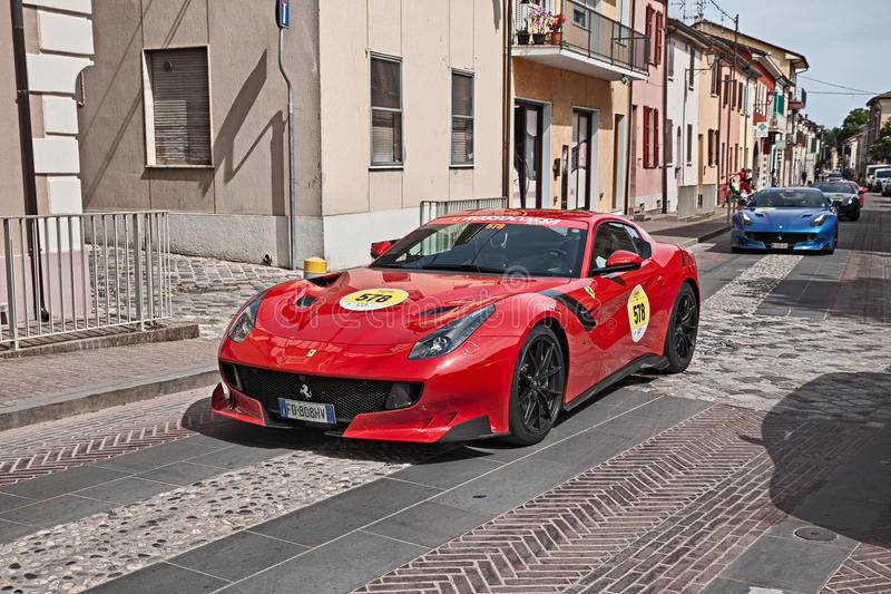 Ferrari F12 TDF 2016 in Mille Miglia 2017. Crew on a supercar Ferrari F12 TDF 2016 in rally `Ferrari tribute to Mille Miglia` during the historical car race royalty free stock photography