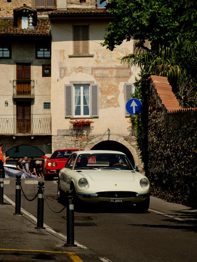 Ferrari 335 GTC at Bergamo Historic Grand Prix 2017. A white Ferrari 335 GTC going down trough Boccola street in Citta` Alta the medieval part of Bergamo during royalty free stock photography