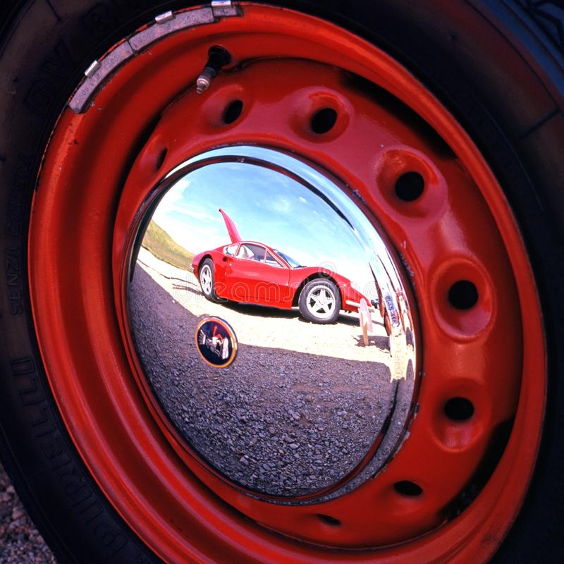 Ferrari reflected in hubcap. A red Ferrari reflected in the hubcap of another vehicle, Gaydon, Warwickshire, England, UK, Western Europe stock photo