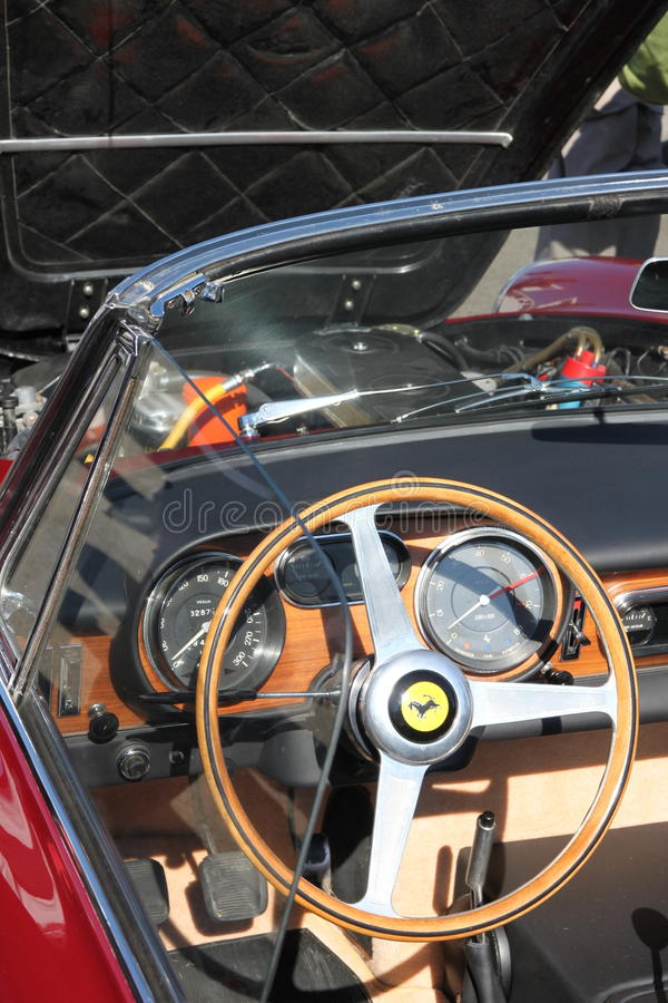 Ferrari steering wheel and dash board of front engined classic car. Ferrari steering wheel and wooden dash board of front engined classic car. Wooden steering royalty free stock photos