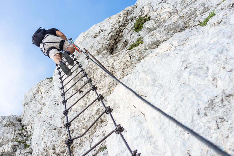 Ferrata - Man climbing a mountain royalty free stock photo