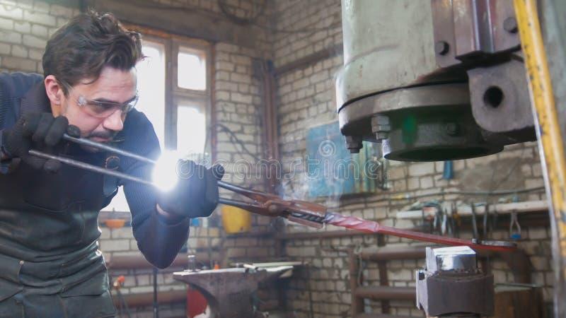 Ferreiro do artesão com um martelo na oficina imagem de stock royalty free
