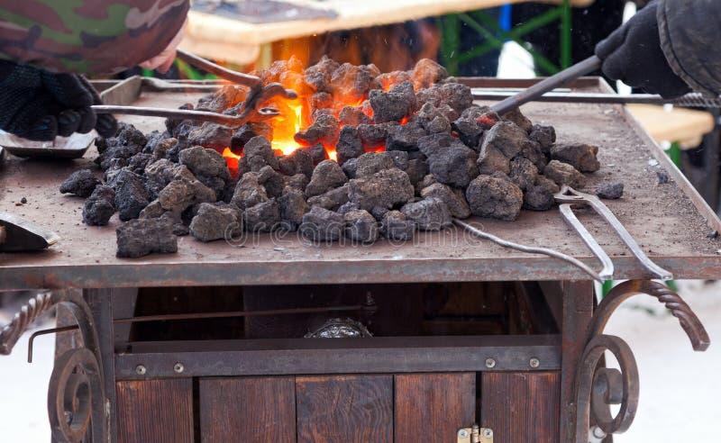 Ferreiro do artesão que aquece uma parte de ferro imagem de stock royalty free