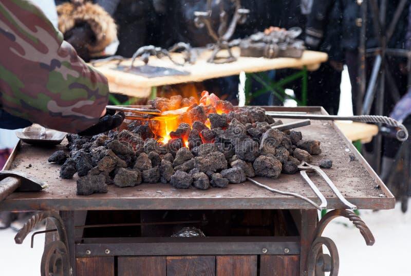 Ferreiro do artesão que aquece uma parte de ferro foto de stock