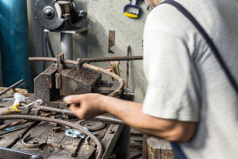 Ferreiro que faz o ferro forjado com a máquina industrial do equipamento do dobrador para a dobra do metal imagens de stock royalty free