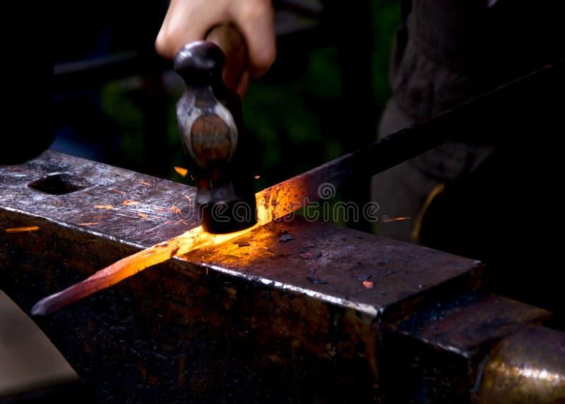 Ferreiro que martela o metal quente imagens de stock royalty free