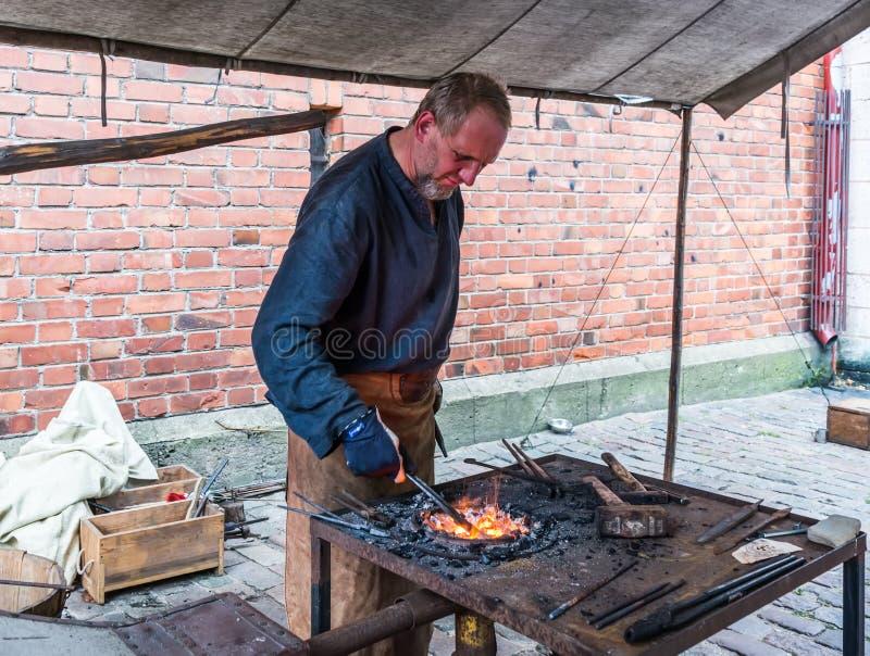 Ferreiro que trabalha no mercado medieval dos ofícios imagens de stock royalty free
