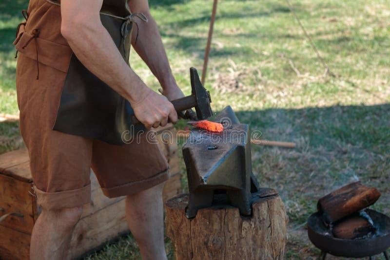 Ferreiro Working Incandescent Iron com martelo e batente foto de stock royalty free