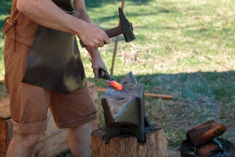 Ferreiro Working Incandescent Iron com martelo e batente imagens de stock