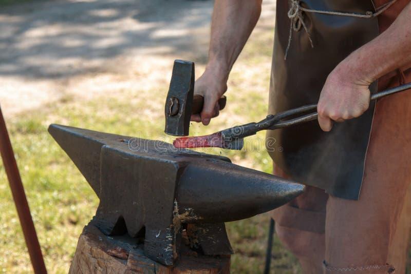 Ferreiro Working Incandescent Iron com martelo e batente foto de stock
