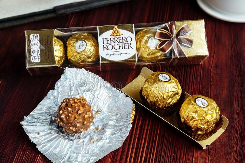 2019-02-05 Ferrero Rocher, los paquetes de lujo tamaño pequeño del bocado del chocolate en la tabla de madera para relaja tiempo foto de archivo libre de regalías