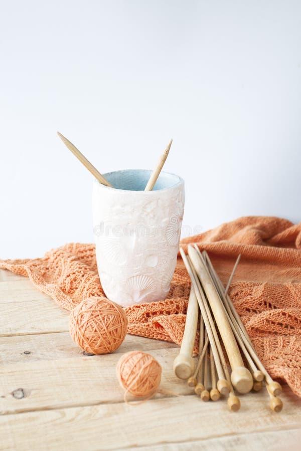 Ferri da maglia di legno, ciuffi del filo, plaid arancio e mano fotografia stock libera da diritti
