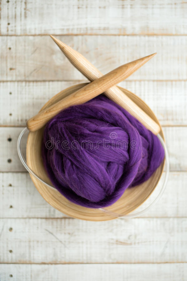 Ferri da maglia di legno e palla porpora della lana merino in un canestro fotografia stock libera da diritti
