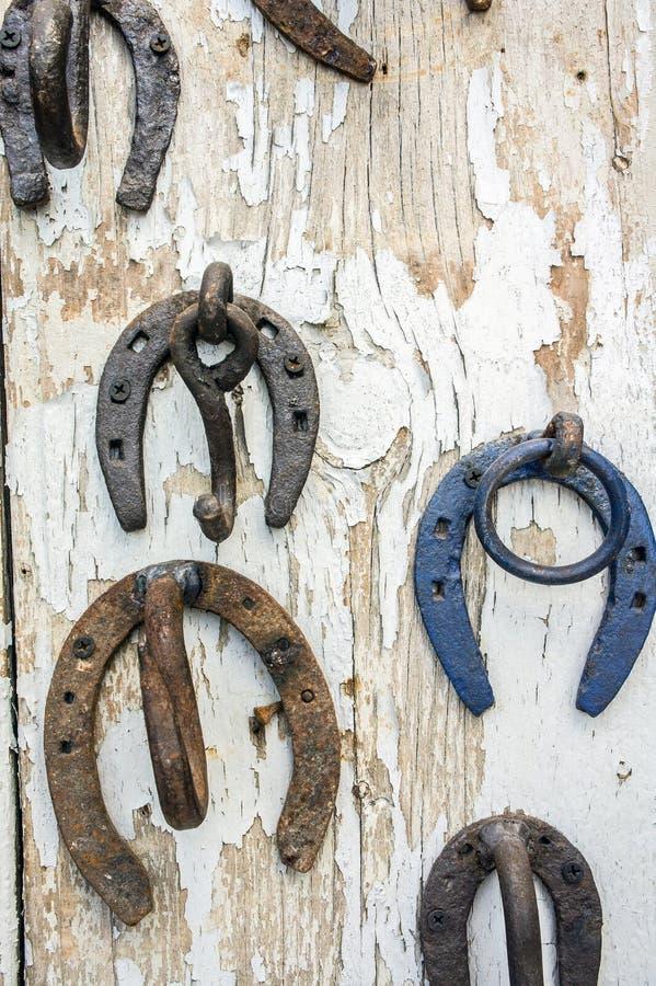 Ferri di cavallo capovolti arrugginiti sul pannello di legno fotografie stock libere da diritti