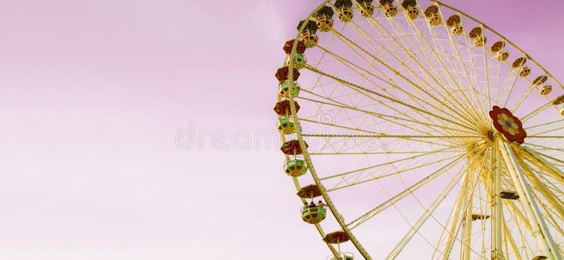 Ferris cud lub koło toczymy wewnątrz parka rozrywki na słonecznym dniu z różowym niebem Fotografia kolor tonujący dla rocznika re zdjęcie stock