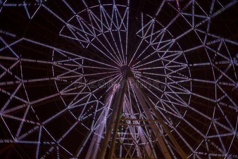 Ferris iluminado roda dentro a opinião da noite do parque fotografia de stock royalty free