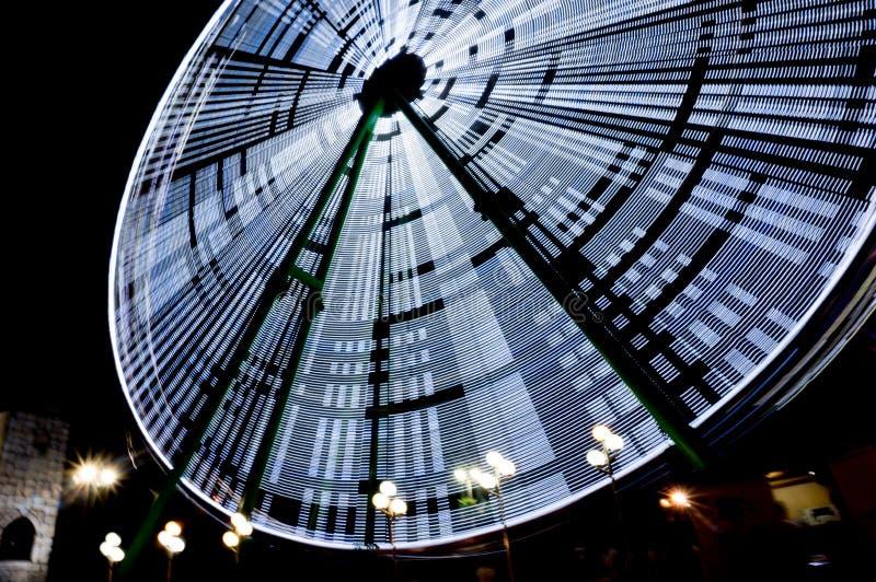 Ferris roda dentro um parque de diversões na noite, exposição longa Conceito do feriado imagens de stock royalty free
