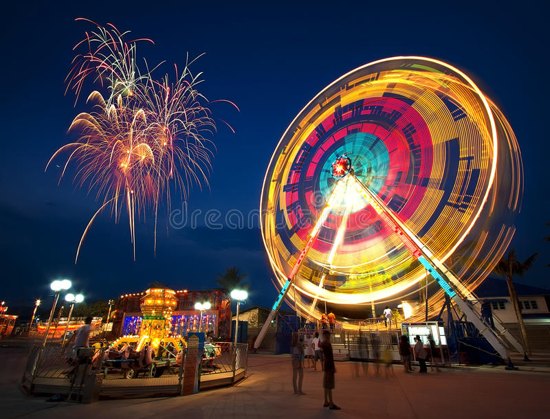 Ferris wheel. Amusement park at night - ferris wheel in motion and firework royalty free stock images
