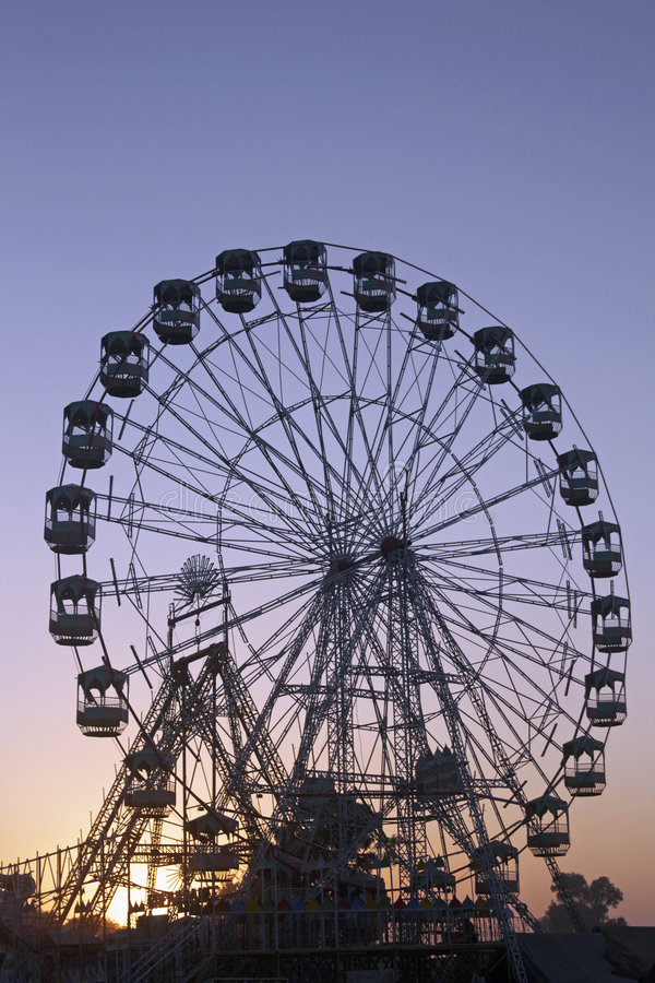 Ferris Wheel. Silhouetted against the darkening sky as the sun sets over the Pushkar fair in Rajasthan, India royalty free stock photo