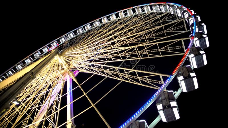 Ferris wheel at amusement park, colorful illuminated construction, bottom view stock photos