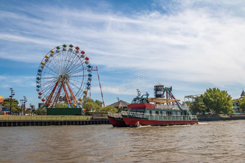 Ferris Wheel, amusement park and ferry boat in Lujan River - Tigre, Buenos Aires, Argentina royalty free stock photos