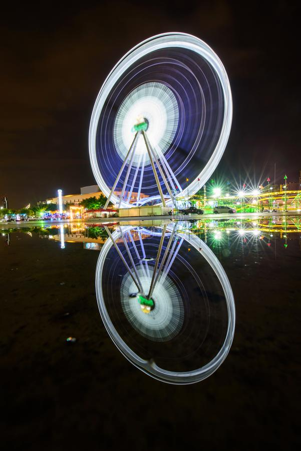Ferris wheel at amusement park with reflections. In night time stock photo