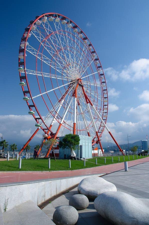 Ferris wheel on Batumi seaside бGeorgia,Adzharia. Ferris wheel on the Batumi seaside on sunny day with beautiful stone-shaped benches,Georgia,Adzharia stock photo