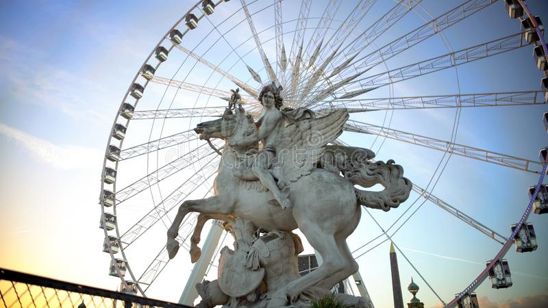 Ferris wheel behind marble statue of equestrian riding winged stallion in Paris royalty free stock photo