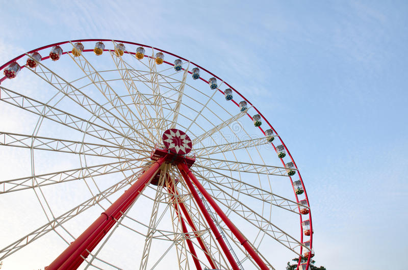 Ferris wheel with cabins on the background of cirrus clouds. A horizontal view stock image