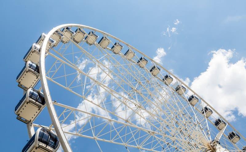 Ferris Wheel Cars on White Wheel. A modern white Ferris wheel against brilliant blue sky royalty free stock photos